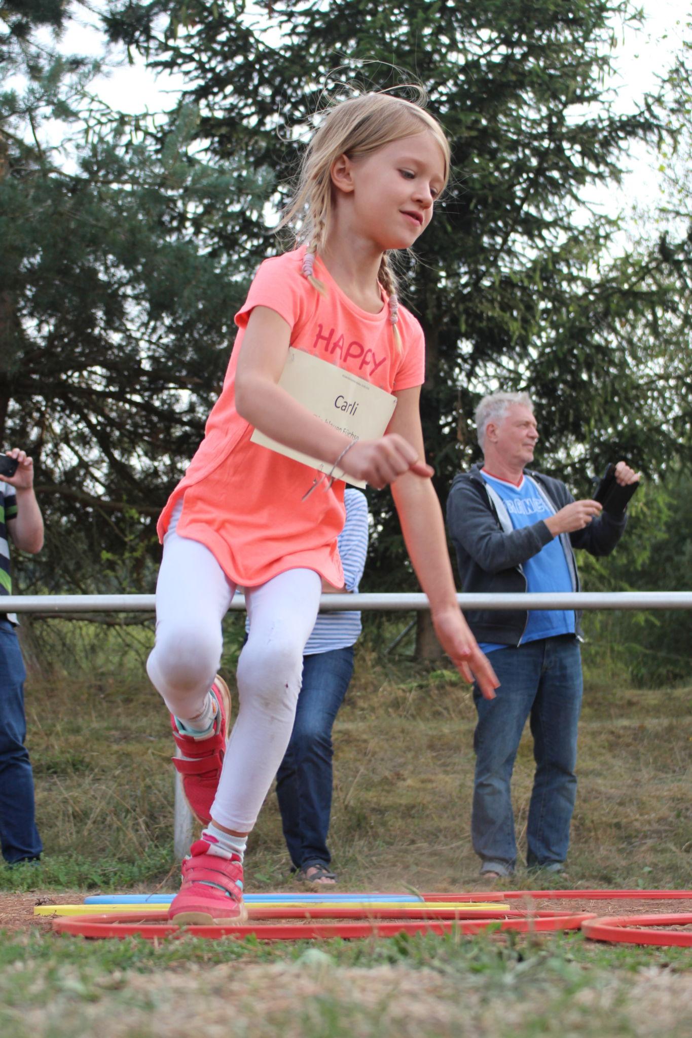 Mädchen springt mit einem Bein in Reifen.