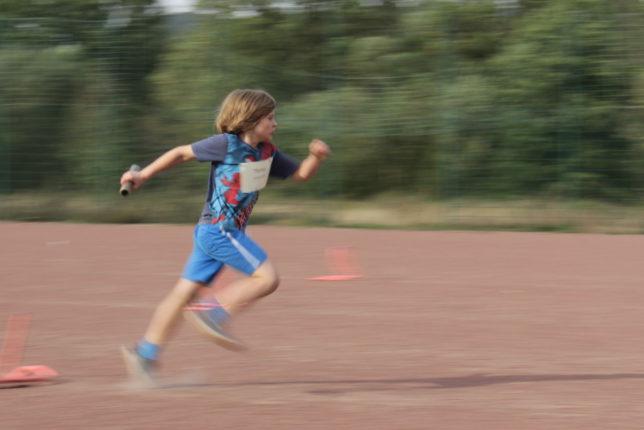 Junge U10 sprintet mit Staffelholz