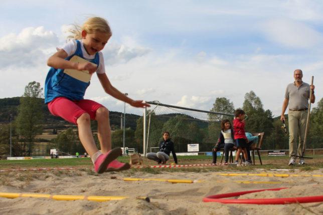 Mädchen U8 springt bei Weitsprungstaffel in einen roten Reifen.